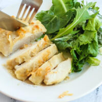 chicken sliced and ready to sat on a plate with salad