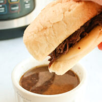 half sandwich about to be dipped into au jus.