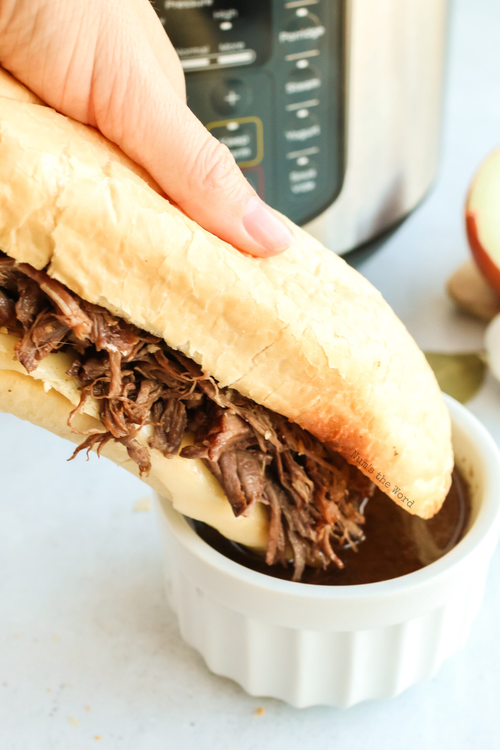 hand holding up a full sandwich about to be dipped into au jus