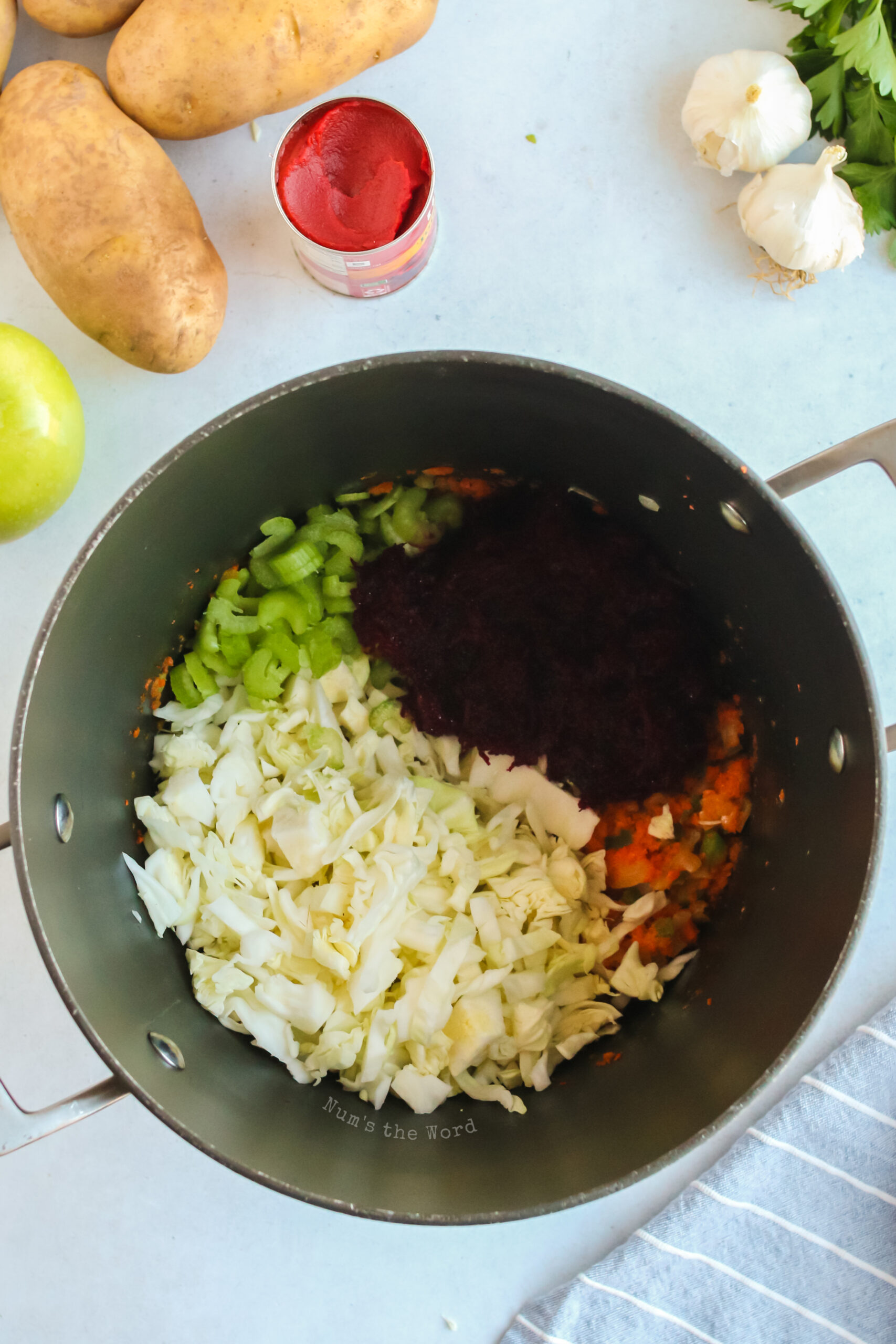 Cabbage, beet and celery added to butter mixture in borscht pot