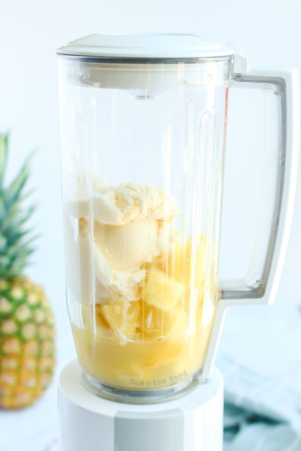 ice cream pineapple juice and frozen pineapple in a blender, unmixed