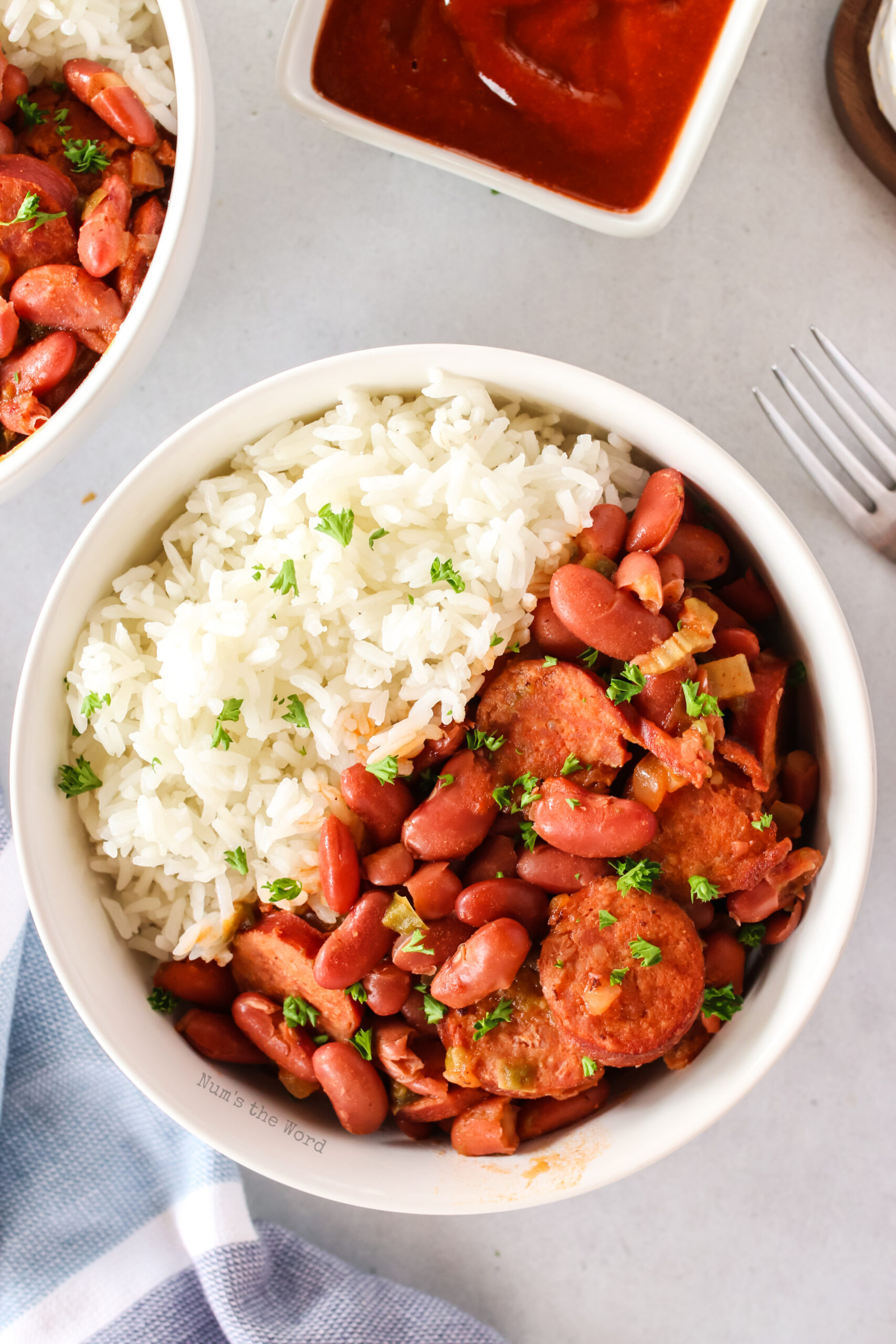 red beans and rice, cooked and in a bowl with rice. Image is taken from the top looking down.