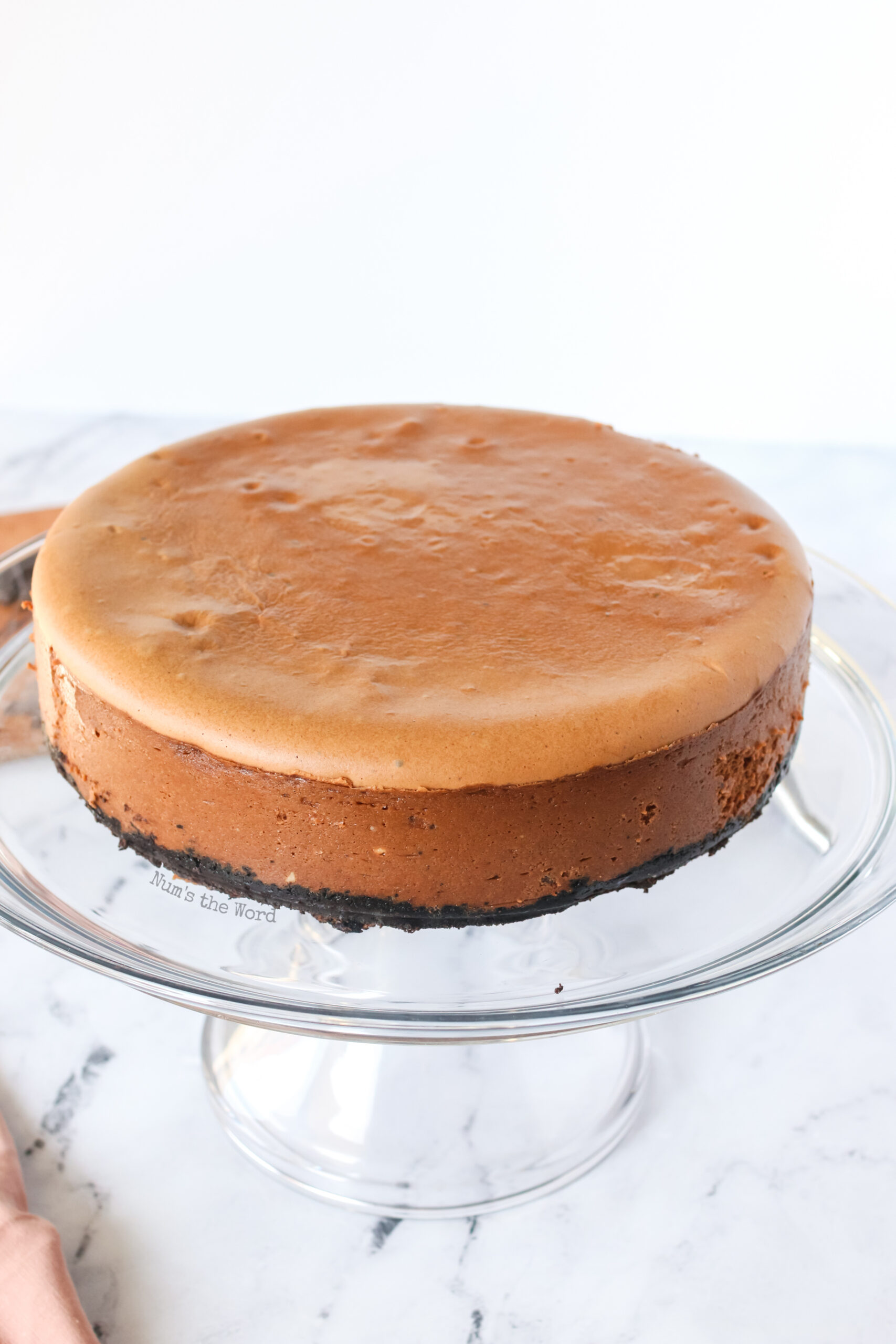 baked and cooled cheesecake on a serving platter.