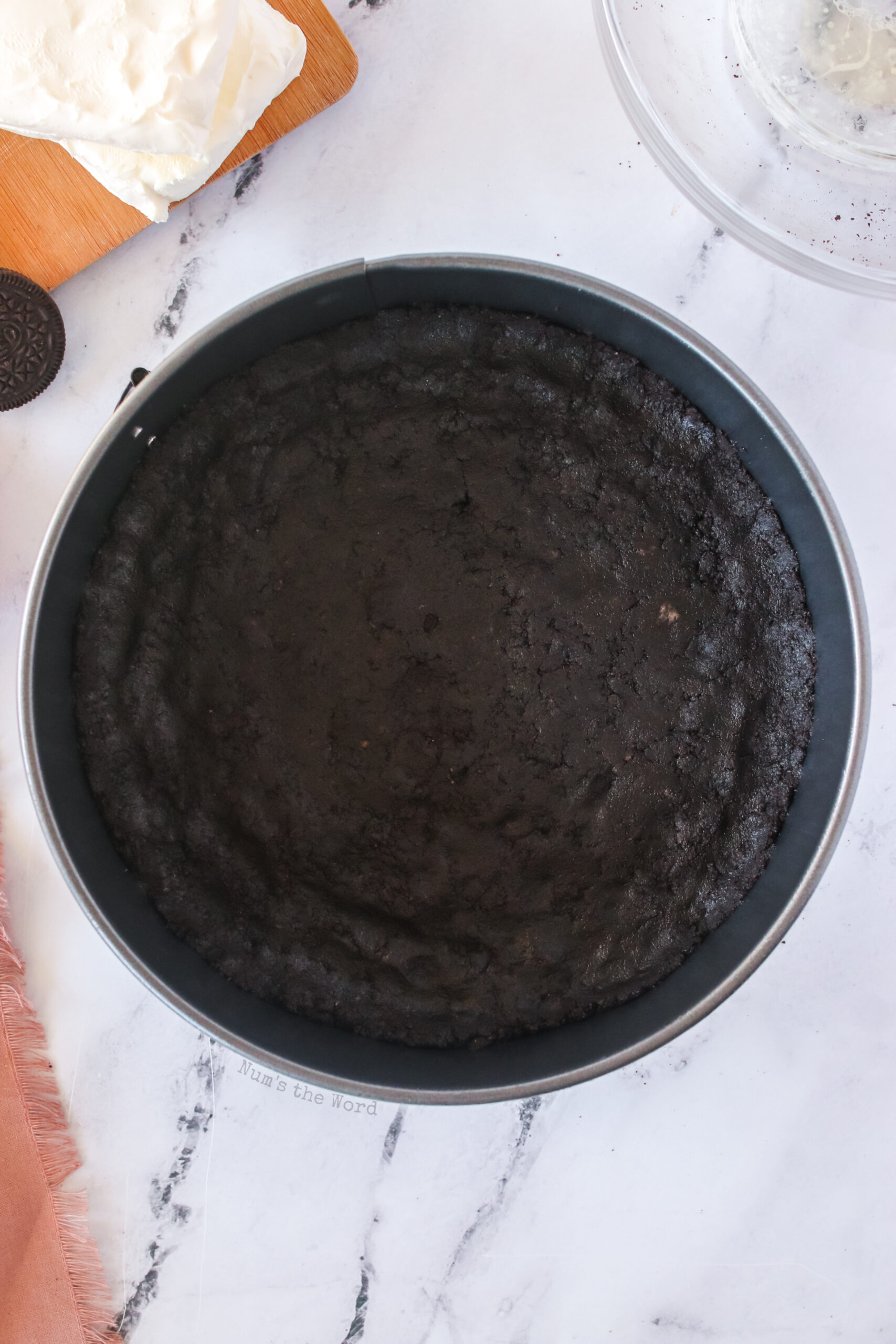 oreo crust added to cheesecake pan and pressed into place.