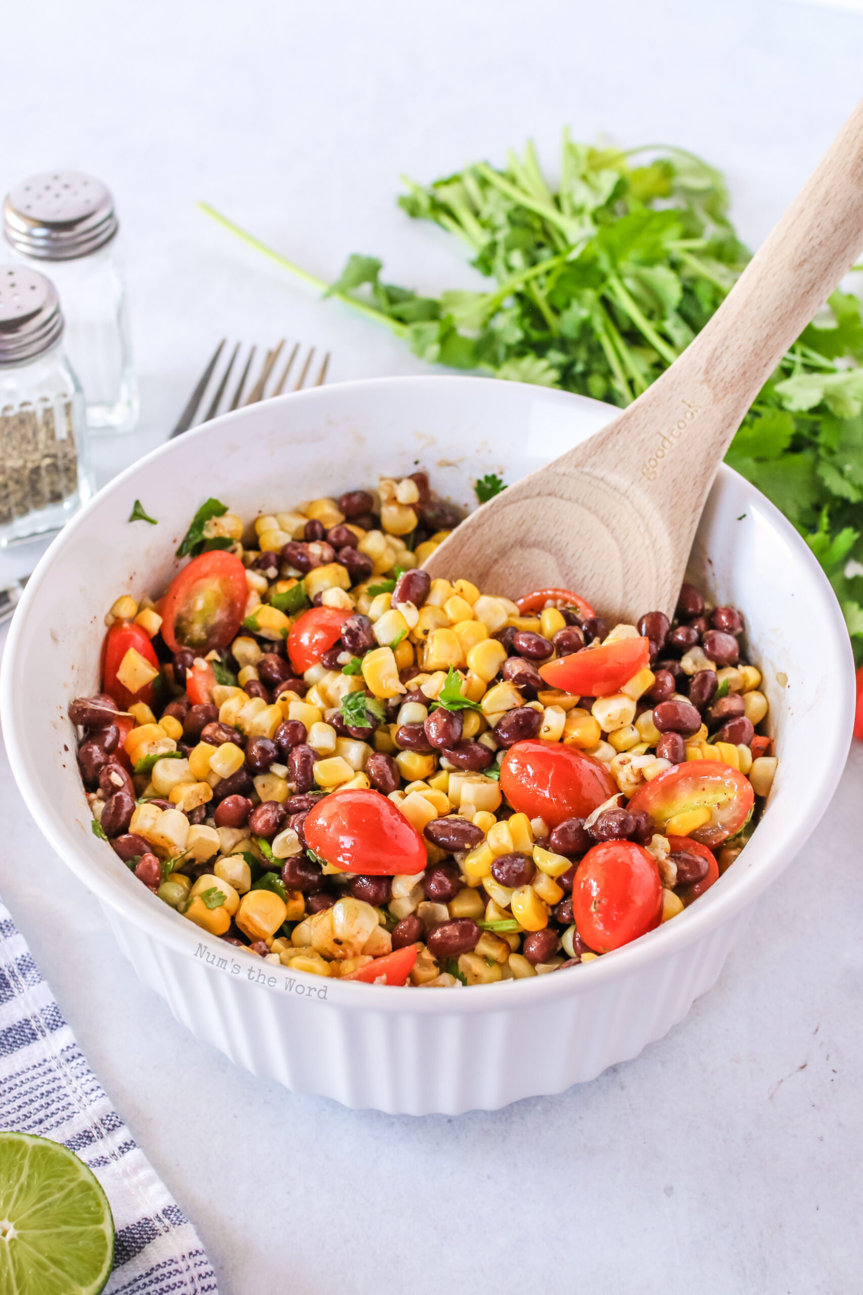 grilled corn salad in a bowl. zoomed out image with wooden spoon.
