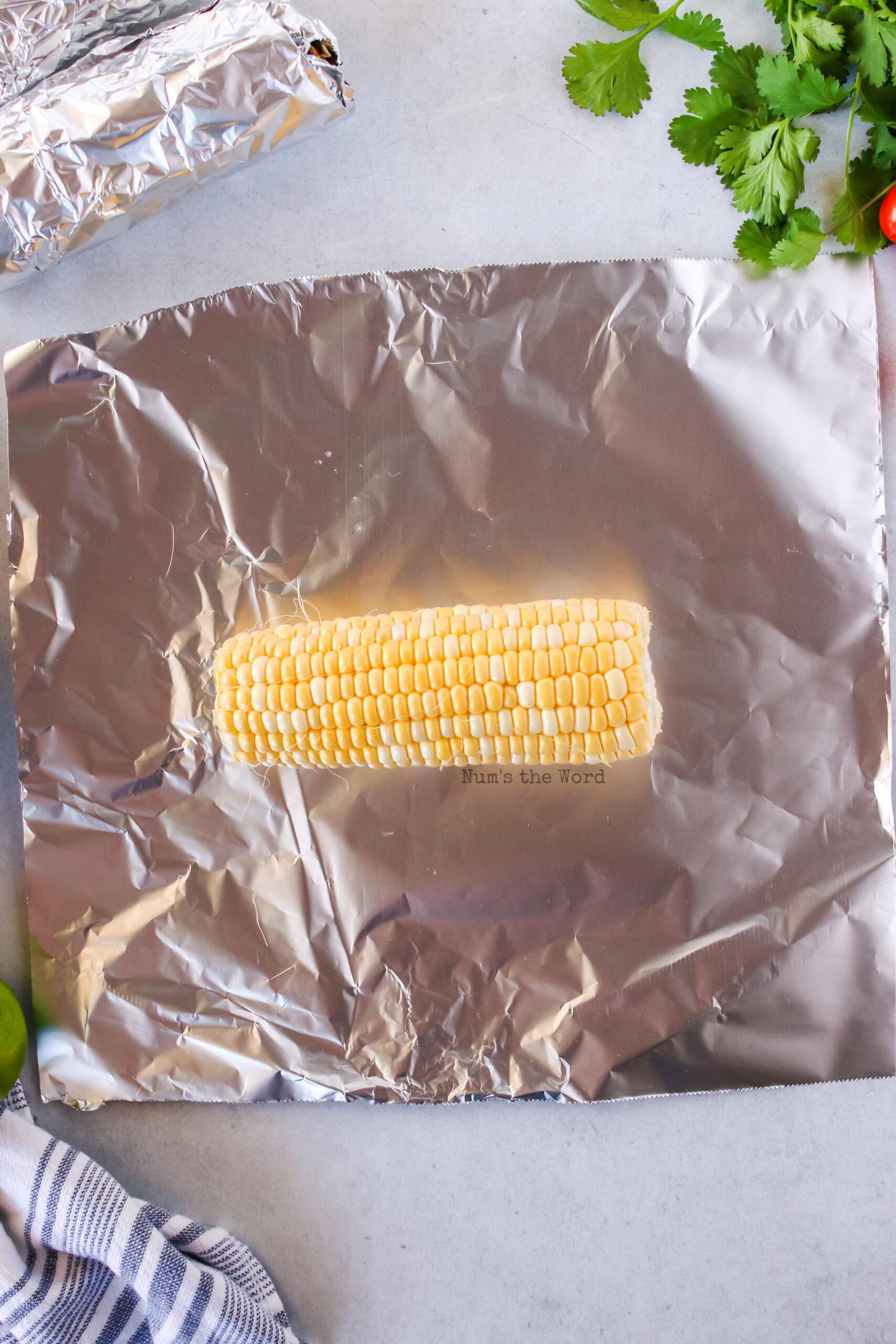 corn cob on top of a piece of foil