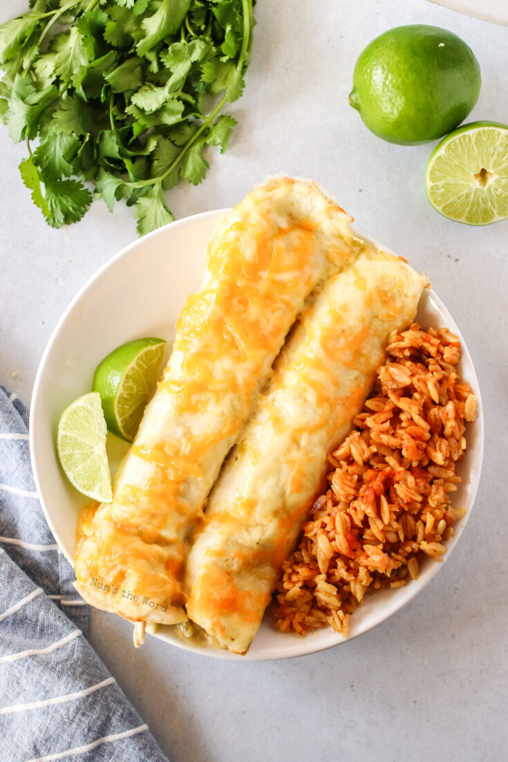 zoomed out image of two enchiladas on a plate with rice and sliced limes. Photo is from the top looking down.