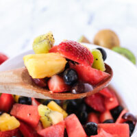 side view of fruit salad in bowl with a wooden spoon holding some above the bowl.