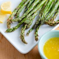 asparagus tips facing camera with bowl of garlic dipping sauce.