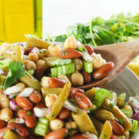 side view image of 3 bean salad in a bowl with a wooden spoon pulling out a serving.