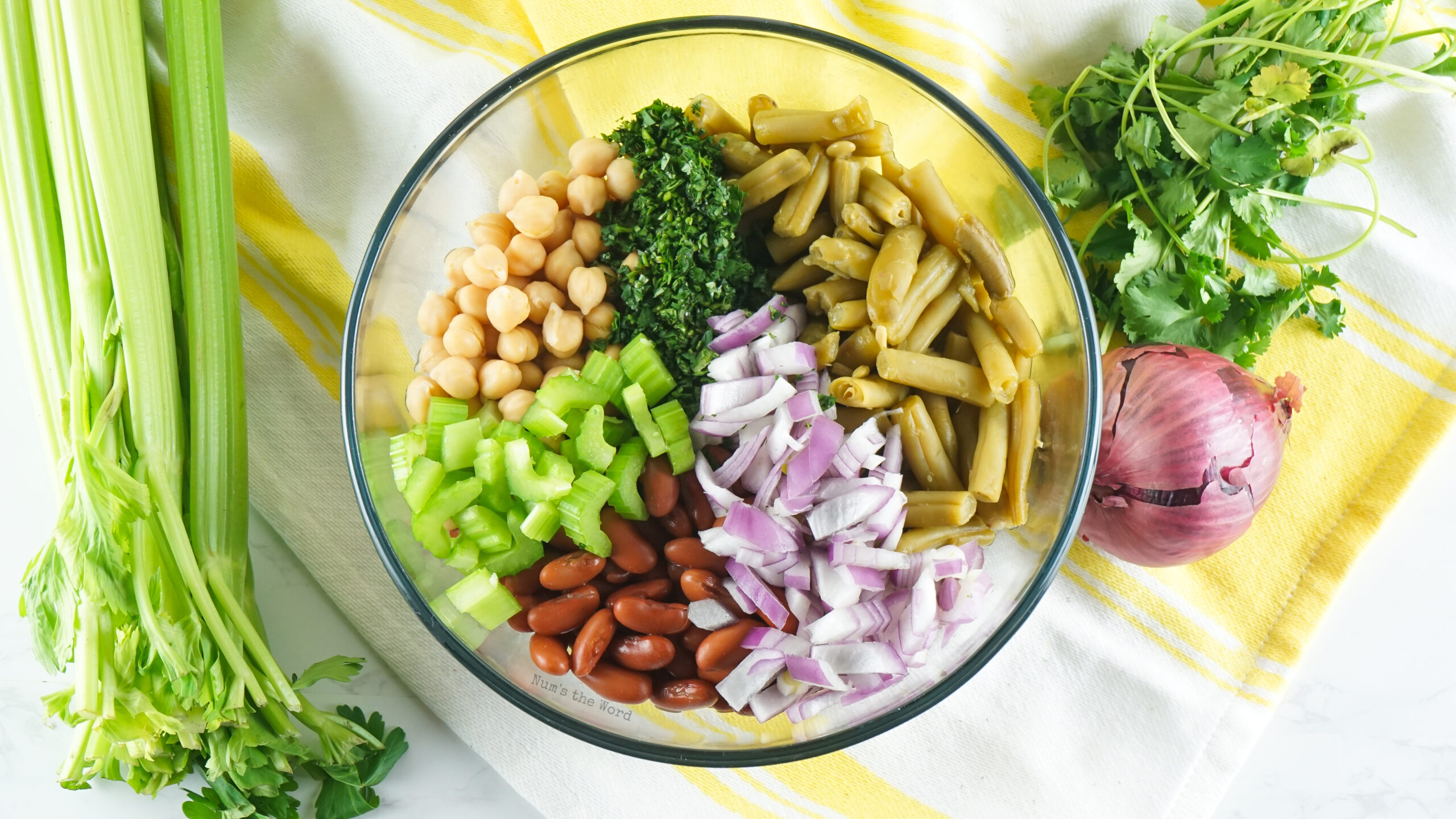 green beans, kidney beans, garbanzo beans, red onion, celery, and cilantro added to a bowl