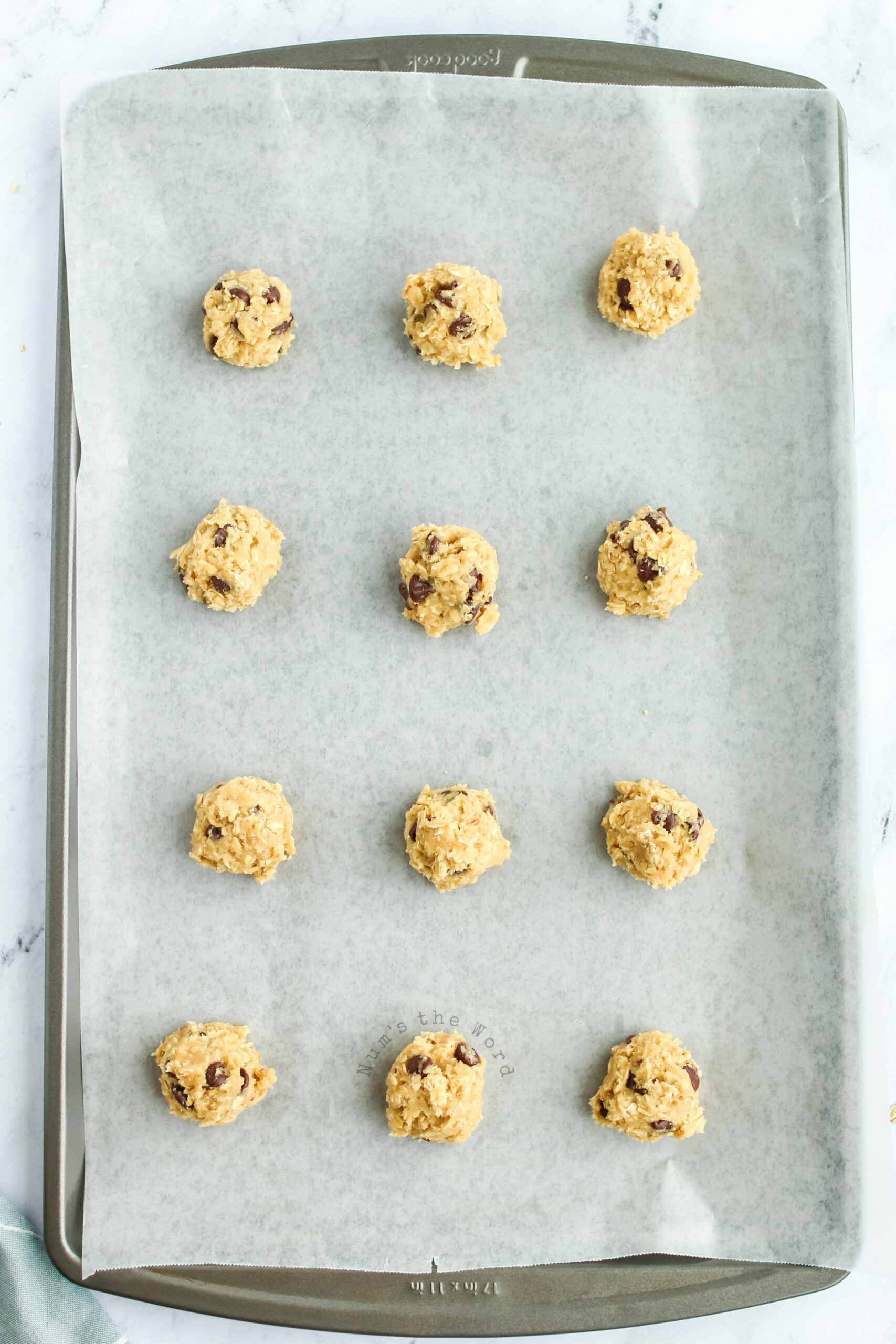 cookie dough balls on a cookie sheet ready to go into the oven.