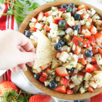 bowl of fruit salsa with a hand scooping out salsa onto a tortilla chip