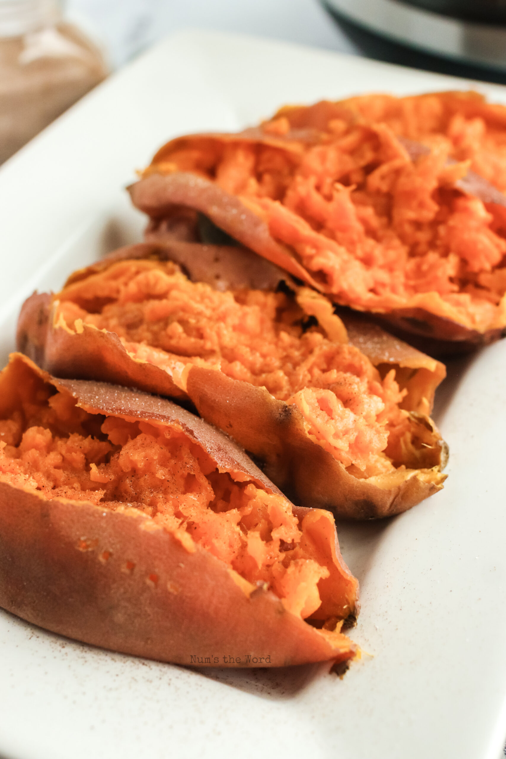 side view of 4 sweet potatoes on a platter, sliced open and ready to serve.