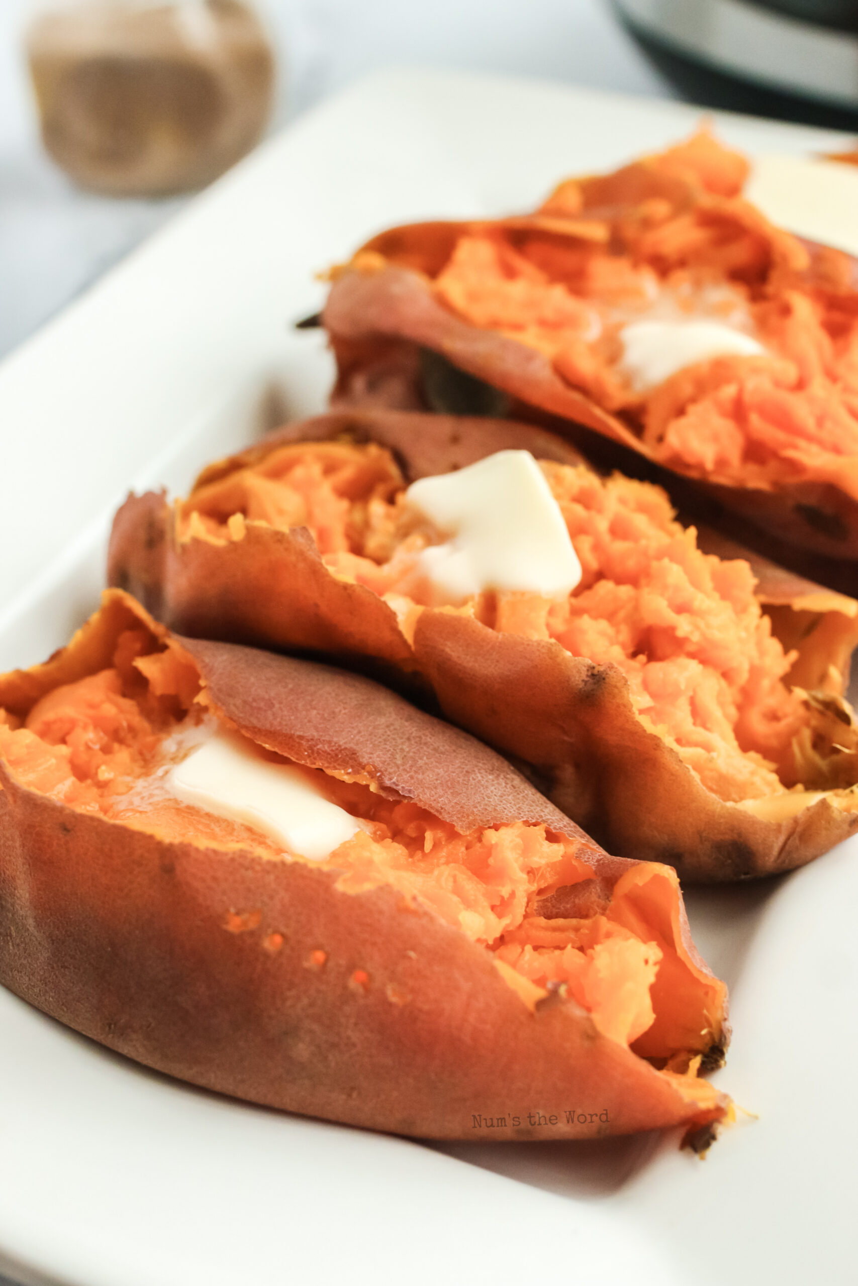 3 sweet potatoes with butter dolloped on top, side view angle