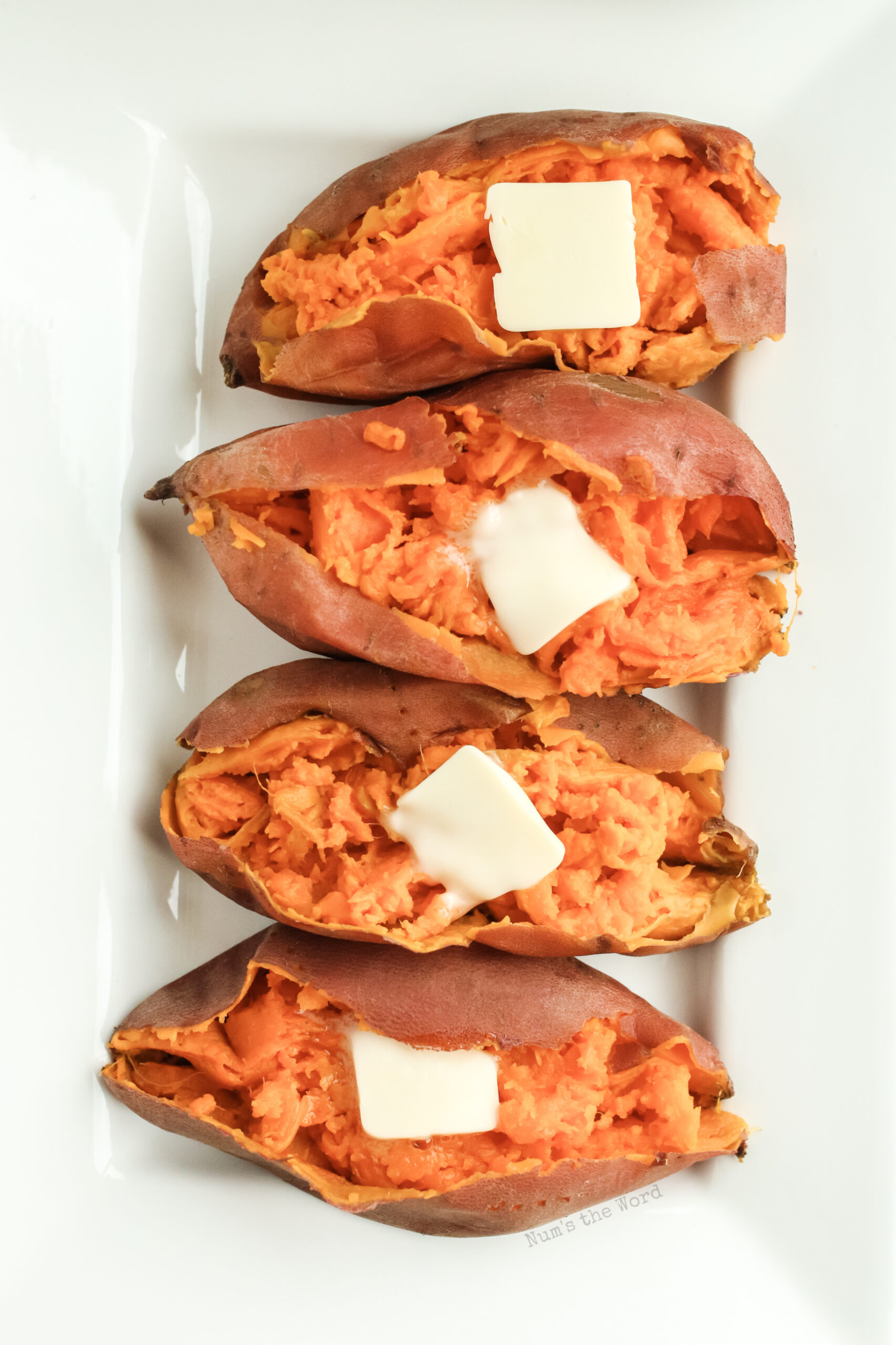 4 sweet potatoes on platter with dollops of butter. Image taken from the top down.