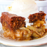 close up of gingerbread cake with apples and ice cream.