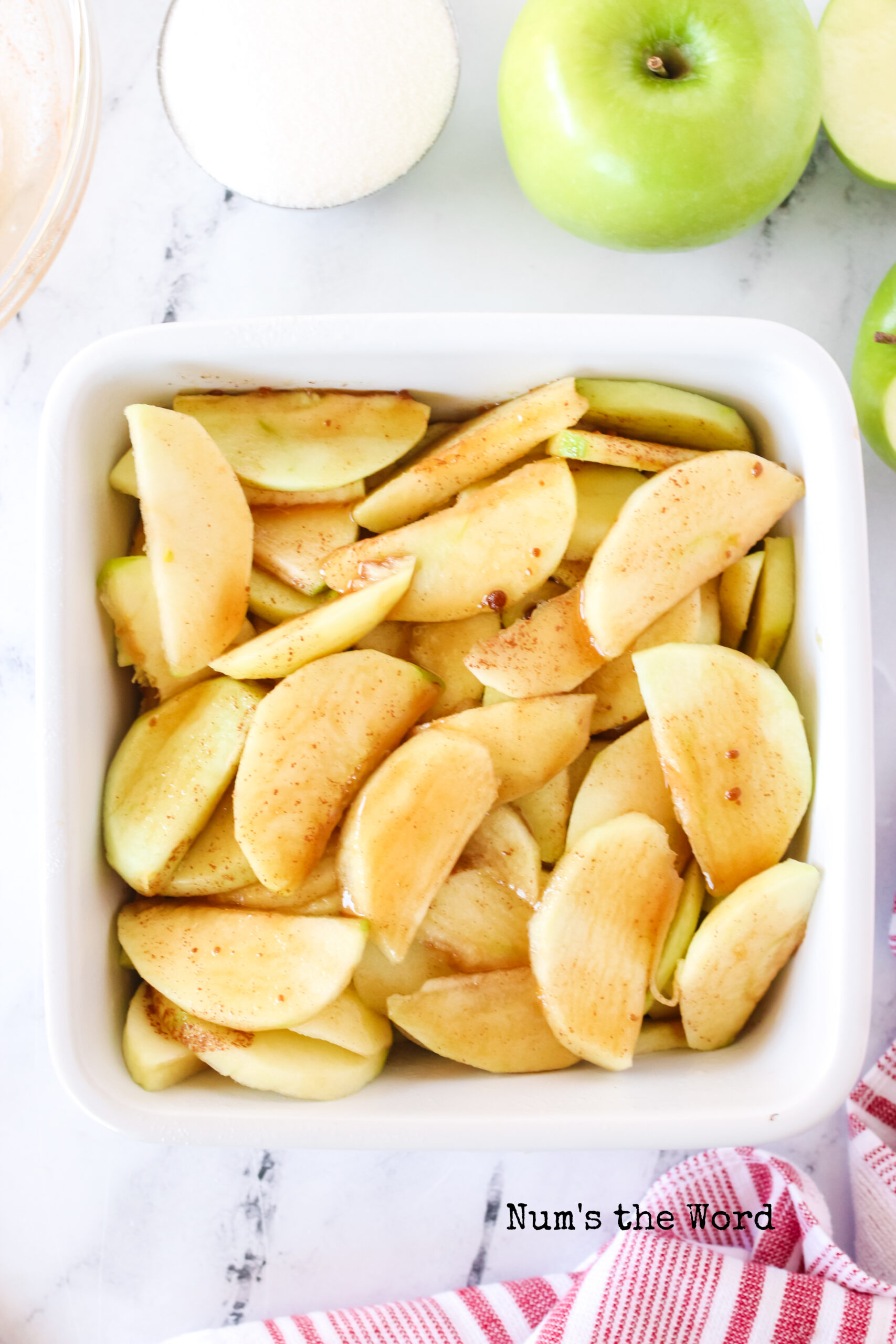 apples sliced and peeled in a casserole dish.
