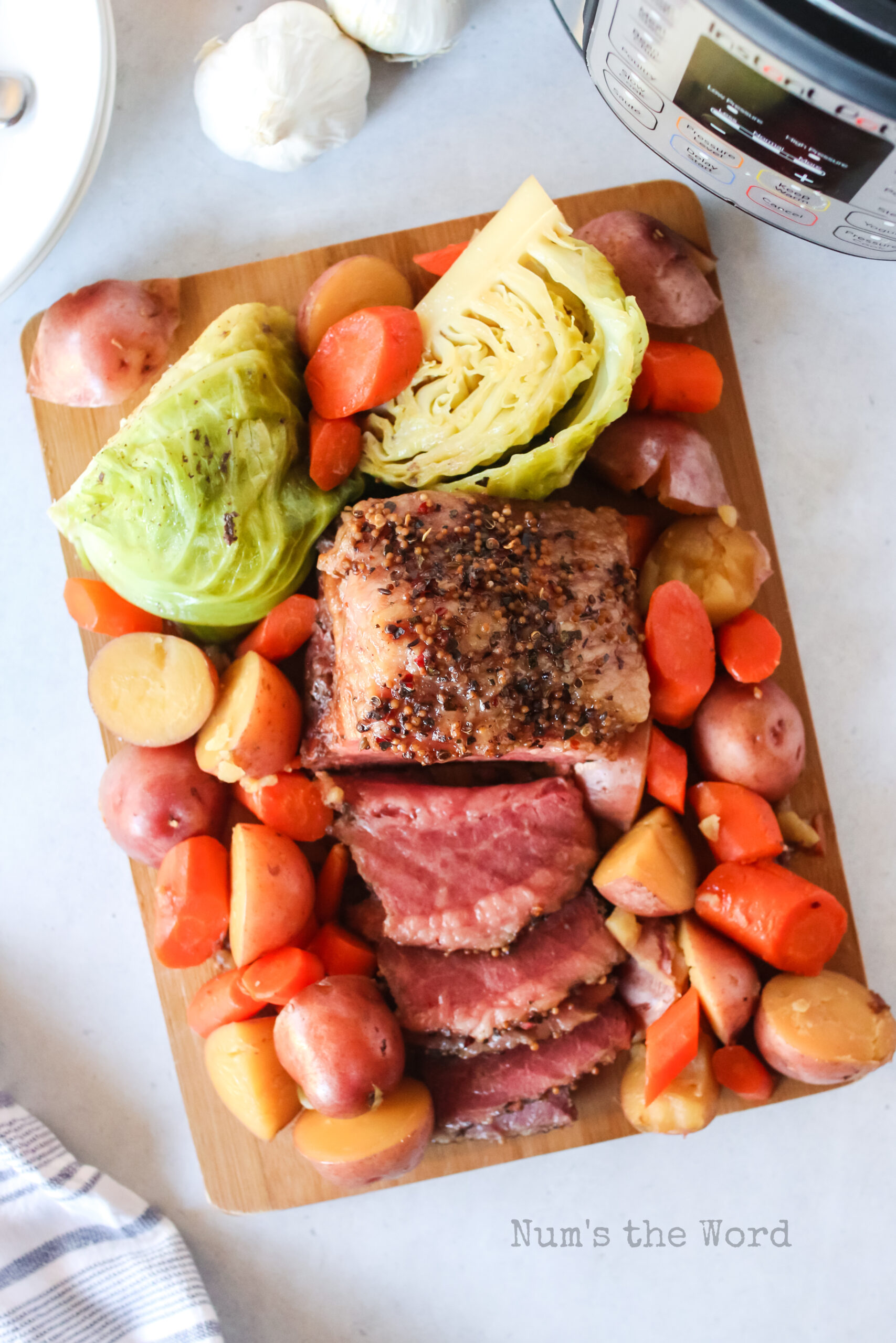 corned beef laid out on a cutting board with cabbage and veggies.