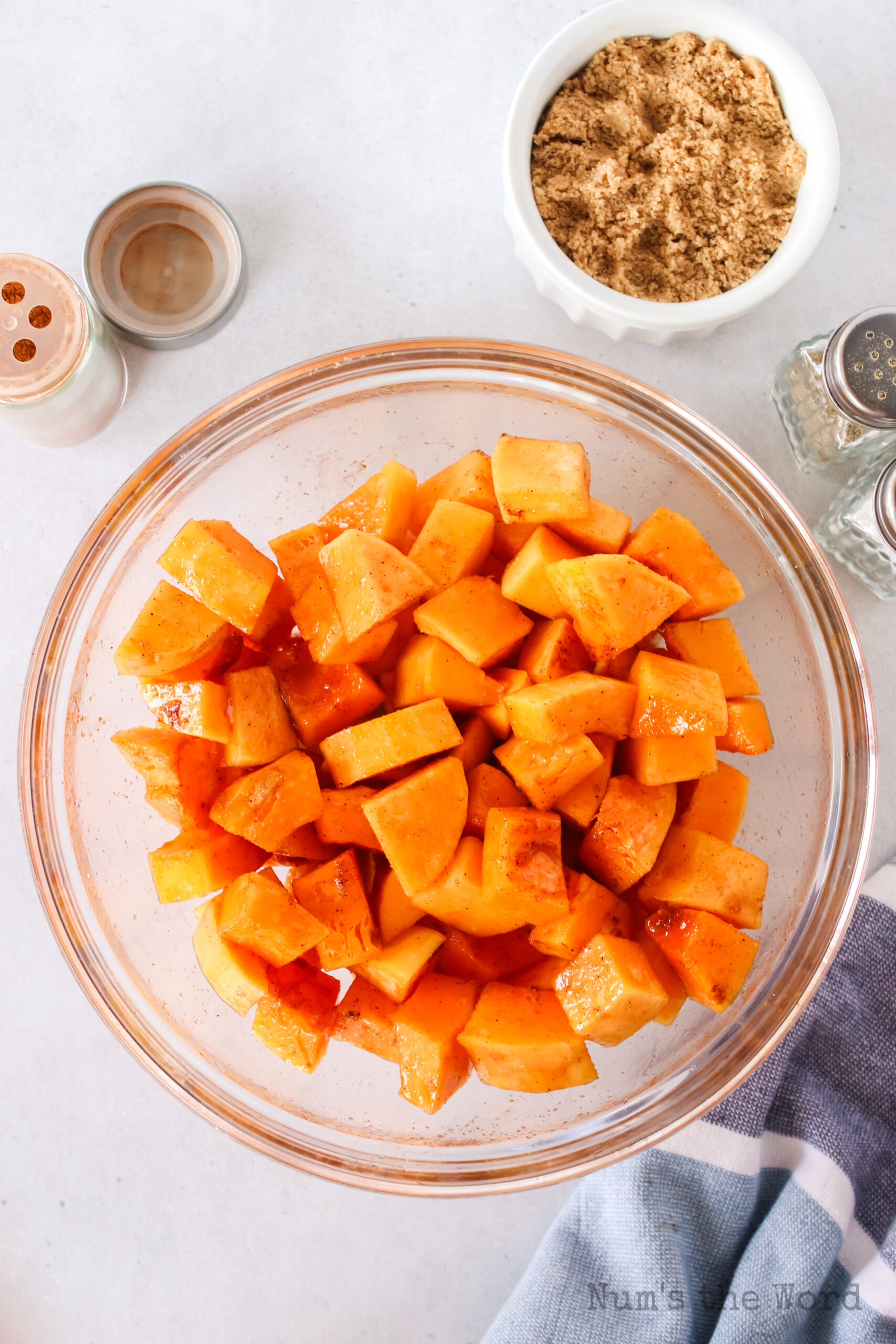 peeled and cut squash in a bowl with oil and seasoning.