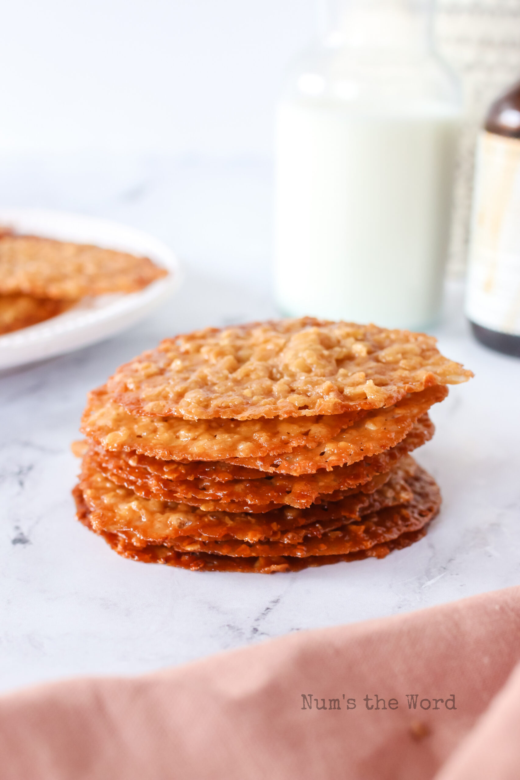 baked cookies stacked up with a glass of milk behind.